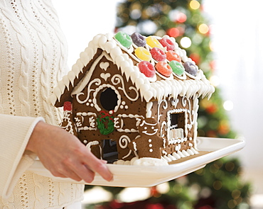 Woman holding gingerbread house on tray