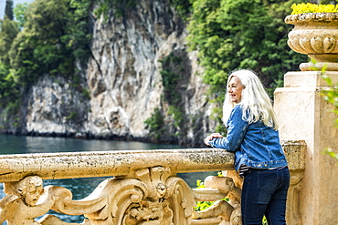 Woman leaning on balustrade at Villa del Balbianello by Lake Como, Italy