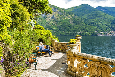 Woman on park bench at Villa del Balbianello by Lake Como, Italy