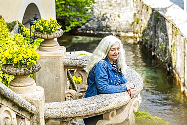 Woman on balcony of Villa del Balbianello by Lake Como, Italy