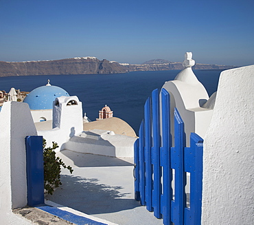 Open blue gate by whitewashed church in Santorini, Cyclades Islands, Greece