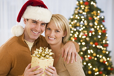 Portrait of couple holding Christmas gift