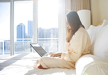 Woman wearing bathrobe using laptop while on phone call