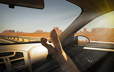 Woman's barefeet on dashboard in Monument Valley Navajo Tribal Park, USA