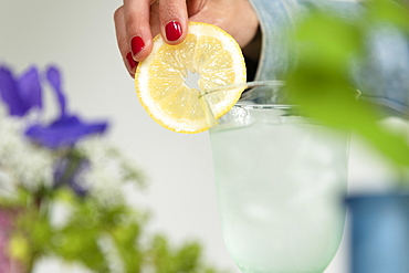 Woman putting lemon slice on glass of water