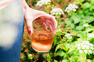 Woman holding glass of rose wine in garden