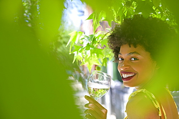 Smiling young woman with glass of white wine under tree