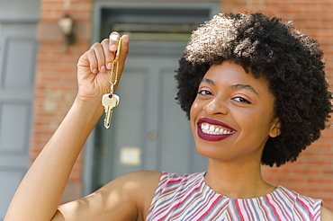 Smiling young woman holding keys