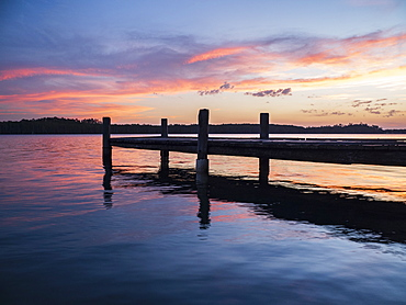 Jetty on river at sunset