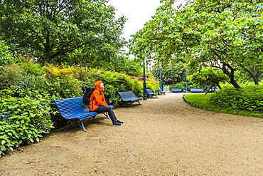 Mature woman wearing raincoat in park in Paris, France