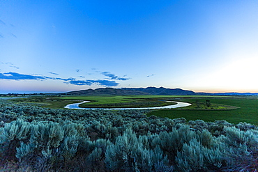 River in field at sunset in Picabo, Idaho, USA
