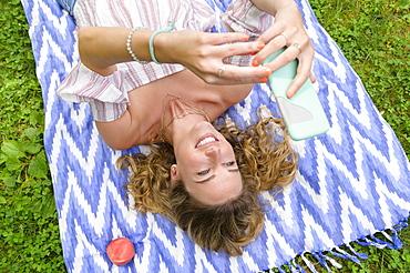 Young woman lying on blanket using smart phone