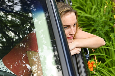 Young woman leaning out of car window