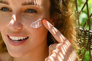 Young woman applying sun cream