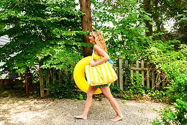 Young woman carrying yellow inflatable and bag