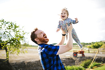 Father lifting baby girl