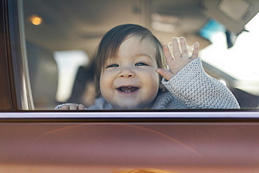 Smiling baby girl behind car window