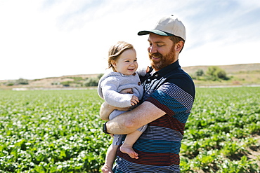 Smiling father holding baby girl in crop field