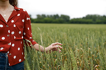 Woman wearing red polka dot shirt in wheat field