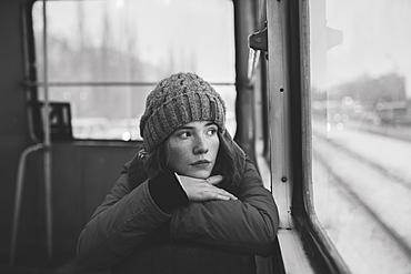Teenage girl wearing woolly hat on train