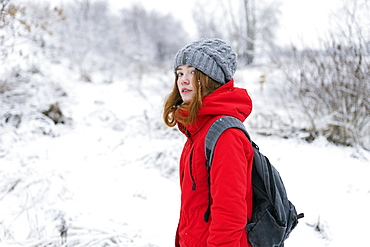 Teenage girl wearing red coat and grey hat in snow