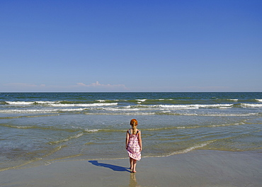 Rear view of girl walking on beach