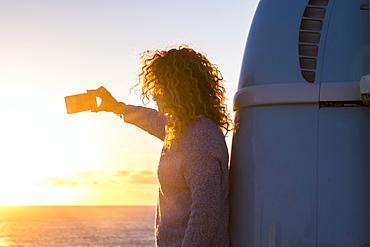 Woman taking selfie by camper van at sunset