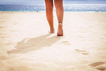 Barefoot woman walking on beach