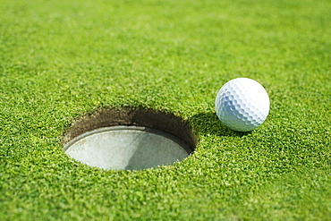 Golf ball near cup on putting green outdoors