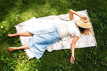 Woman lying on blanket in park