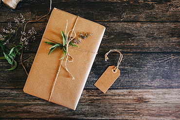 Present wrapped in brown paper and string with label and flowers