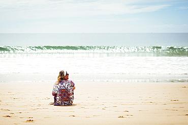 Woman sitting on beach in Lisbon, Portugal