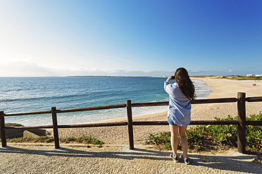 Woman photographing beach in Lisbon, Portugal