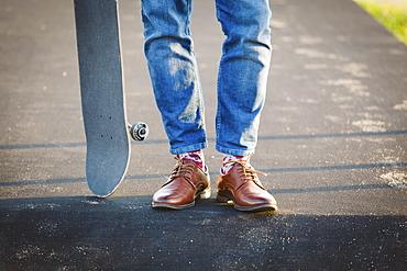 Feet of man with skateboard on footpath