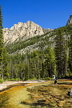 Woman wading through river by Sawtooth Mountains in Stanley, Idaho, USA