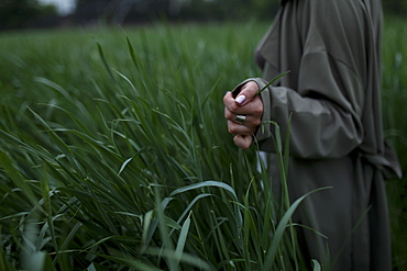 Woman wearing green coat walking through field