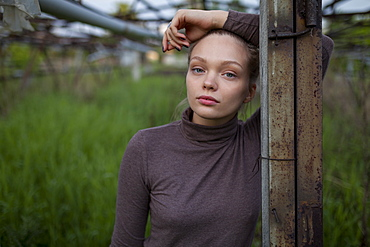 Young woman leaning on wooden post