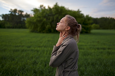 Young woman with her eyes closed in field