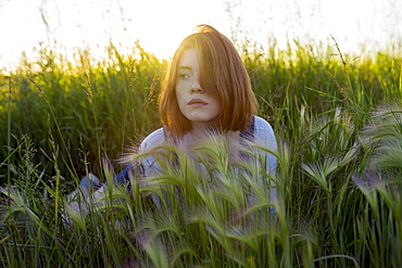 Young woman lying in wheat field