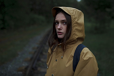 Young woman wearing brown raincoat