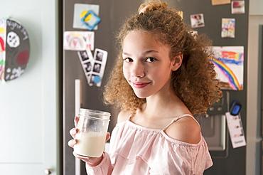 Girl holding glass of milk in kitchen