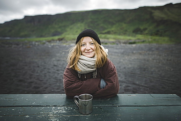 Young woman wearing warm clothing at picnic table on beach