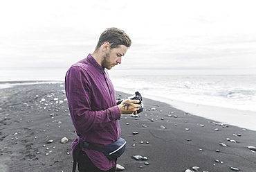 Man holding camera on beach in Iceland