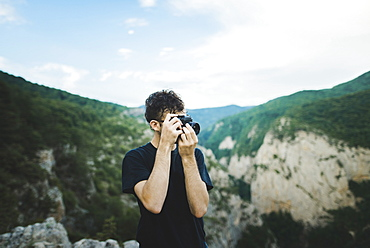 Man photographing with camera by mountains in Crimea, Ukraine