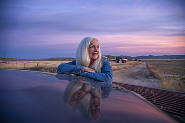 Woman leaning on car at sunset in Boise, Idaho, United States of America