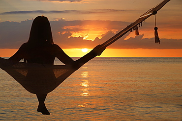 Woman sitting in hammock at sunset at Miami Beach in Miami, Florida, United States of America