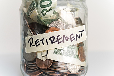 Money in jar labeled 'retirement'