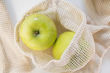 Green apples in reusable bag