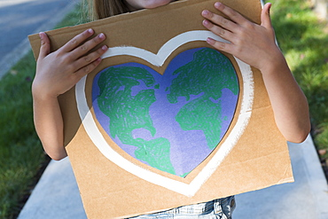 Young environmental activist holding sign
