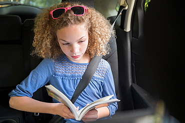 Girl reading book in car